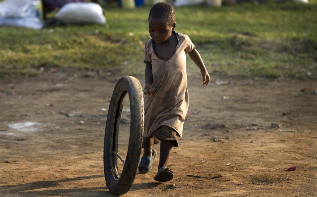 Flicka lekar med gammalt hjul, Goma DRC.
